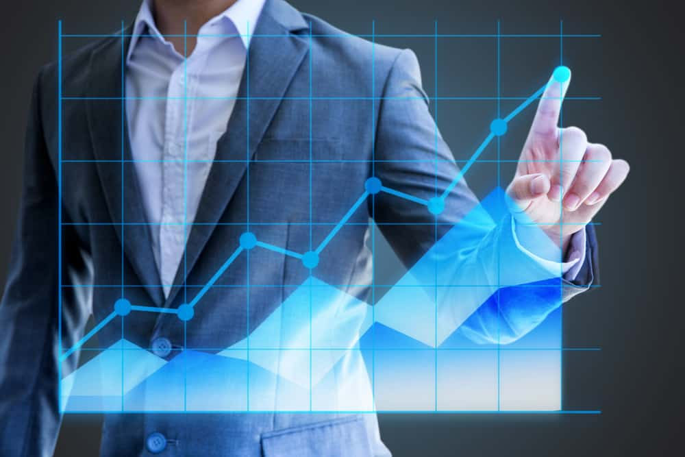 Businessman use hand show line graph holographic statistics. Source: Shutterstock.com