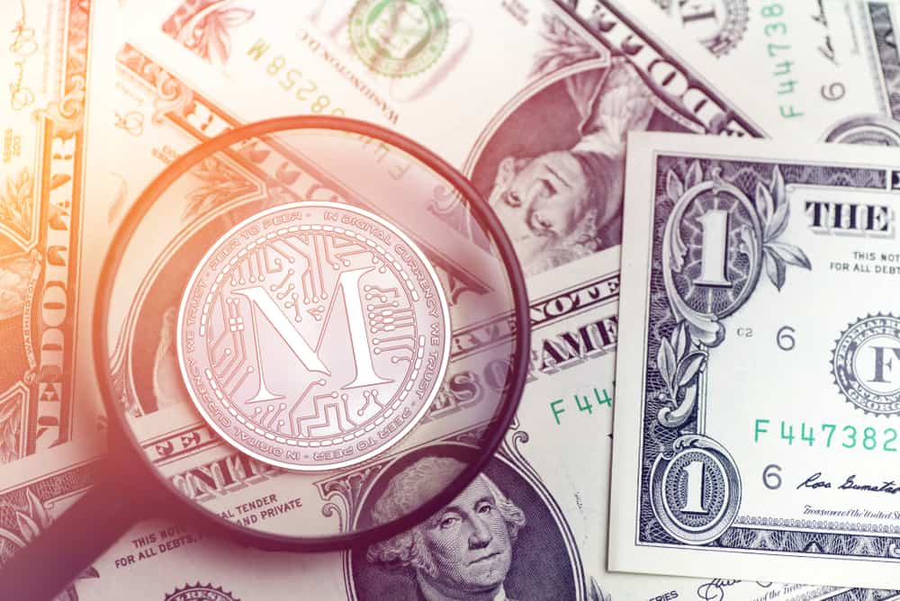 MAECENAS cryptocurrency coin on blurry background with dollar money. Source: Shutterstock.com
