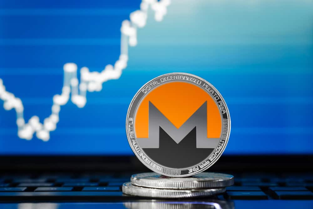 Silver monero coin on the background of the chart. Shutterstock.com