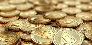 Stack of golden EOS coins in blurry closeup with copy space above in blurred area. Source: Shutterstock.com