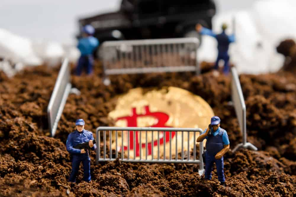 miniature policeman officers stand watch over bitcoin in fence. digital virtual cryptocurrency money blockchain concept. Sources: shutterstock.com