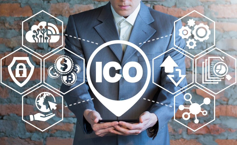 A man holding a smartphone with ICO. Source: Shutterstock.