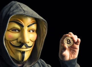 MILAN,ITALY, February, 2018: Hacker hold golden bitcoin coin and wear anonymus mask .Editorial photo. Source: shutterstock.com