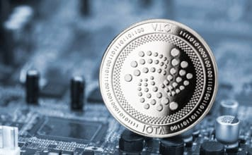 iota silver coin on blue motherboard chip digital mining computer hardware crypto currency financial background concept