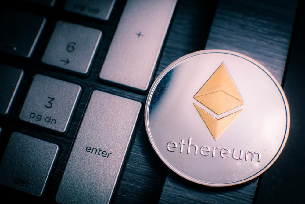 Ethereum cryptocurrency (crypto currency). Silver Ethereum coin with gold Ethereum symbol on a laptop keyboard next to the Enter key. SOurce: shutterstock.com
