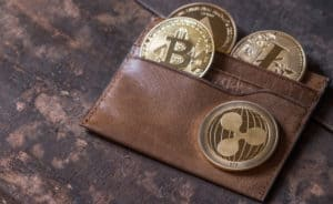 Popular cryptocurrency in leather wallet on wooden table top. Source; shutterstock.com