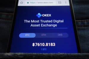KONSKIE, POLAND - JUNE 02, 2018: OKEX cryptocurrency exchange website displayed on smartphone hidden in jeans pocket. Source; shutterstock.com