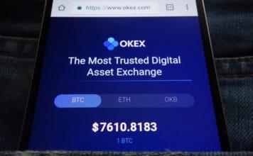 KONSKIE, POLAND - JUNE 02, 2018: OKEX cryptocurrency exchange website displayed on smartphone hidden in jeans pocket. Source; shutterstock.com