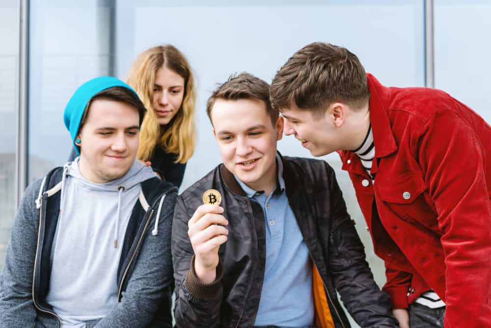 Young man showing crypto token to friends