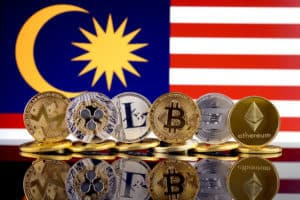Physical version of Cryptocurrencies (Monero, Ripple, Litecoin, Bitcoin, Dash, Ethereum) and Malaysia Flag. Source: shutterstock.com