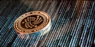 One golden Iota coin on a background of black and blue computer and binary code. Source: shutterstock.com