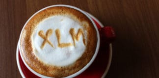 Coffee Cappuccino in a red cup with a symbol of Stellar Lumens XLM on milk foam. Source: shutterstock.com
