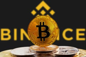 Bitcoin BTC on stack of cryptocurrencies with Binance exchange logo in background. The cryptocurrency coin is golden and in focus. Copenhagen / Denmark - 07 12 2018. Source; shutterstock.com