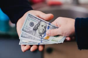 Transfer of money from hand to hand - Source: ShutterStock.com
