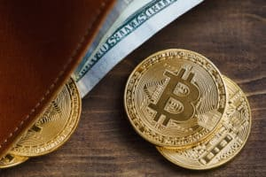 Top view of a purse with gold coins bitcoin. The concept of the crypto currency. Source: shutterstock.com
