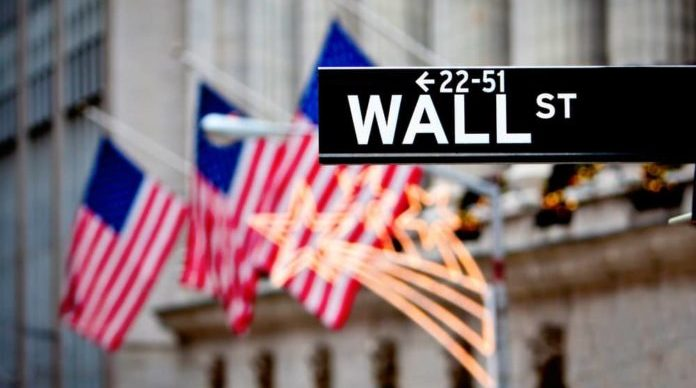 Wall street sign in New York with New York Stock Exchange background - Source: ShutterStock.com