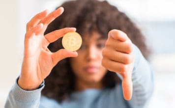 African american woman holding golden bitcoin cryptocurrency at home with angry face, negative sign showing dislike with thumbs down, rejection concept Source; shutterstock.com
