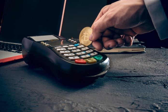 Bitcoin, credit card and POS-terminal. The golden bitcoin in male hands. Cryptocurrency bitcoin coins. Litecoin, Bitcoin, Ethereum, e-commerce, busibess, finance concept. crypto currency symbol. Source: shutterstock.com