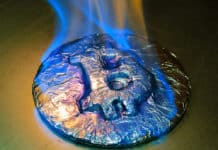 Bitcoin metal silver coin is burning with blue flame. It means hot price or value and high exchange rate of crypto currency on market. It is crisis and fall to lose investments due to financial risk. Source: shutterstock.com