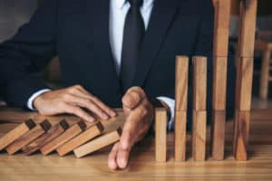 Close up of businessman hand Stopping Falling wooden Dominoes effect from continuous toppled or risk, strategy and successful intervention concept for business. Source: shutterstock.com