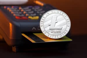 Litecoin cryptocurrency payment system, litecoin token lying on a credit card inserted in a terminal payment machine card reader. Source: shutterstock.com
