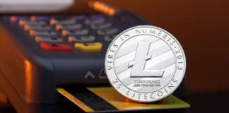 Litecoin cryptocurrency payment system, litecoin token lying on a credit card inserted in a terminal payment machine card reader.