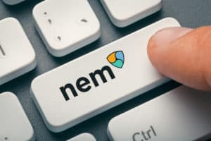 finger pressing computer key with nem coin logo. crypto mining concept. Source: shutterstock.com