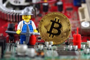 WROCLAW, POLAND - SEPTEMBER 01, 2018: Physical version of Bitcoin, miner (as Lego figure) and integrated circuit on background. High technology concept. Source: shutterstock.com