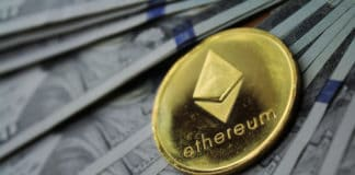 Gold Ethereum Ether ETH on hundred dollars bills. Close-up, macro shot. Source: shutterstock.com