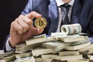 Businessman receive a lot of Money from Smartphone, Businessman Holding Bitcoin Isolated on black background, Digital Money and Bitcoine Concept. Source; shutterstock.com