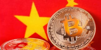 Bitcoin real coins over chinese flag fabric. Source; shutterstock.com