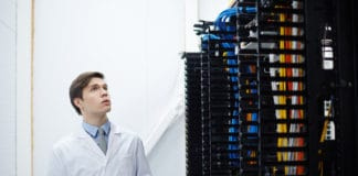 Engineer of data center looking at new bitcoin hardware while working in storage room. Source; shutterstock.com