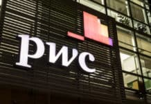 MILAN ITALY - APRIL 15, 2017 The logo of PricewaterhouseCoopers on the office building of the Italian headquarters in Milan. Nigth view. Source: shutterstock.com