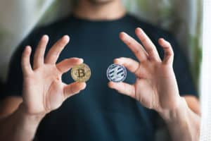 Man holds in hands two physical cryptocurrency coins - golden bitcoin and silver litecoin. Source; shutterstock.com