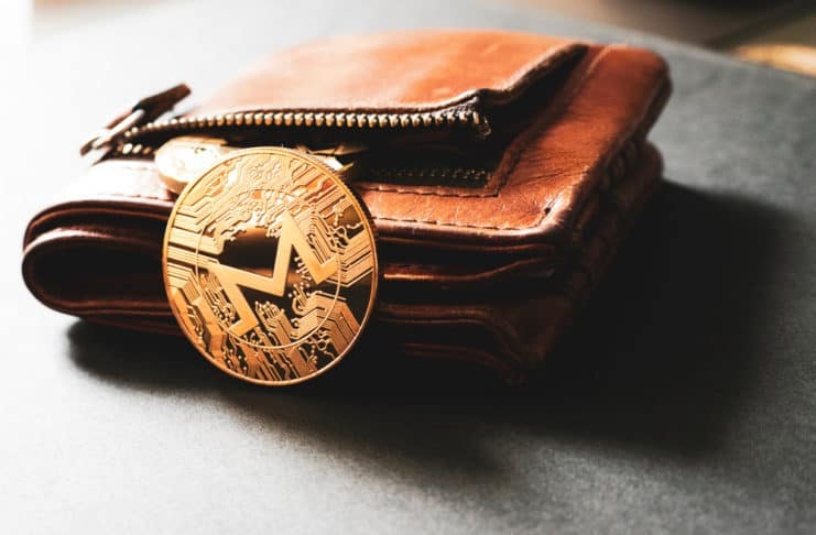 One golden Monero coin leaning against an open leather wallet on a plain surface. Source: shutterstock.com