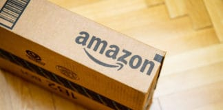 PARIS, FRANCE - JAN 28, 2016 Amazon logotype printed on cardboard box side seen from above on a wooden parwuet floor. Amazon is an American electronic e-commerce company distribution worlwide. Source; shutterstock.com