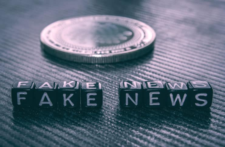 Words fake news from black dice and silver coin dark background. Source: shutterstock.com