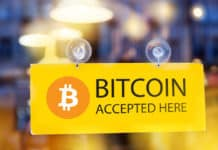 virtual money Bitcoin cryptocurrency - Bitcoins accepted here - logo of bitcoin on restaurant glass door. Source: shutterstock.com