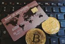 Bitcoin and credit card on a black computer keyboard. Online payments, virtual currency and computer technology concept.