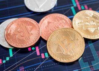 Cryptocurrency Bitcoin coins over tablet screen showing candlestick chart.