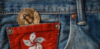 Golden BITCOIN (BTC) cryptocurrency in the pocket of jeans with the flag of Hong Kong