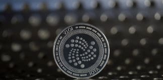 Iota cryptocurrency physical coin placed on the metal surface with holes
