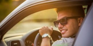 Portrait of young cheerful male in car