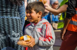 Athens APRIL 15 Syrian boy receive oranges from Charitable Organizations in a refugee camp April 15, 2016 in Athens. - Image