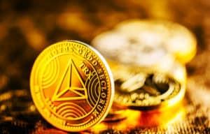 Closeup of golden tron coin TRX cryptocurrency over black and gold background. Virtual money altcoin and blockchain concept. - Image