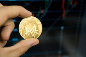 Male businessman hand holding Monero coin on a background of growth graph on a screen of laptop. Virtual money and Financial growth concept on chart background. Trading Mining of moneros coins.