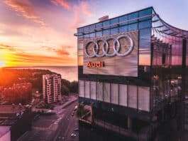 TALLINN, ESTONIA - JULY 2016 Aerial drone shot of the the Audi logo on the outside glass facade on the big office skyscraper building in Tallinn at sunset. Audi is a German automobile manufacturer. - Image