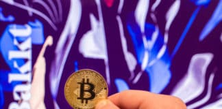 SLOVENIA - DECEMBER 24, 2018 Bitcoin coin in front of Bakkt website. - Image