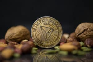 Tron TRX cryptocurrency physical coin surrounded with variety of nuts, including walnuts, hazelnuts, almonds and pumpkin seeds in the black background - Image