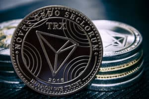The coin cryptocurrency Tron on the background of a stack of coins. - Image